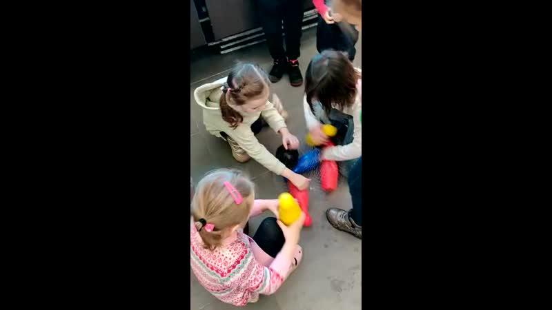 Аниматор Алиса в стране чудес играет с детьми в кегли