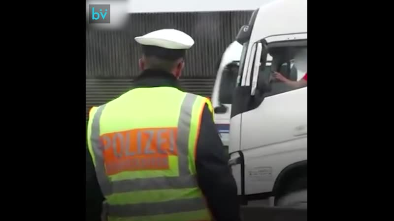 Немецкий полицейский и люди, снимающие место ДТП